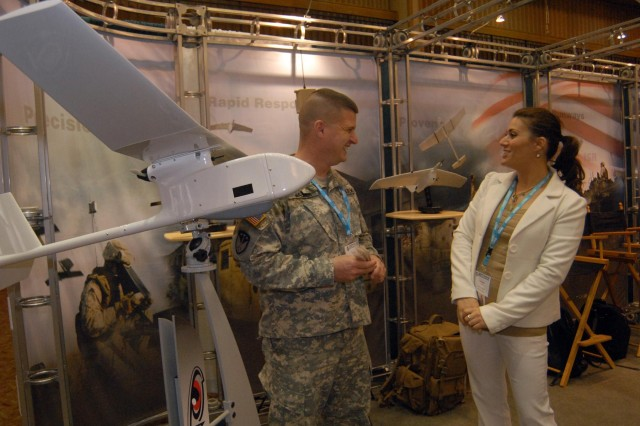 Lt. Col. Robb Walker of the Unmanned Aircraft Systems Project Office talks with Charlotte Johnson of Aerovironment about the development of various unmanned aircraft systems. Several industry partners are developing unmanned aircraft systems that they hope will have a future role in the Department of Defense's unmanned aircraft systems roadmap.