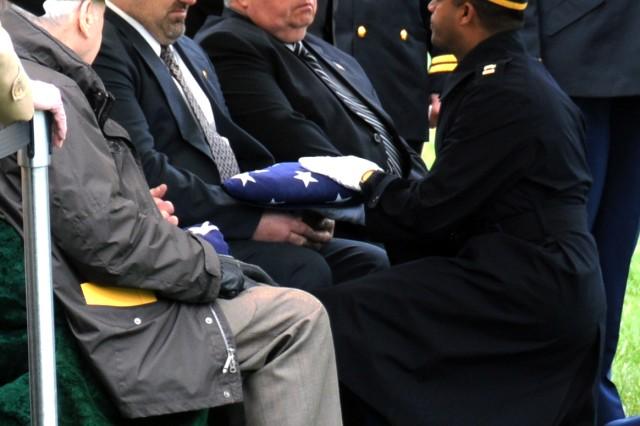 A family member representing 1st Lt. Richard T. Heuss receives the flag.