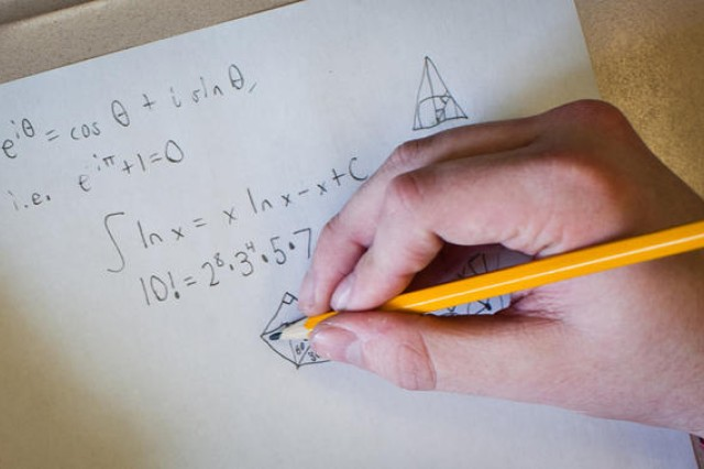 Meade High School senior Logan Crew, a member of the high school's math club, writes out an equation that was solved in the annual math competition hosted by Anne Arundel Community College. The 17-year-old, a student in the school's International Baccalaureate program, was the top-scoring individual in the contest and was awarded the Donald Wertz Memorial Book Award. (Photo by