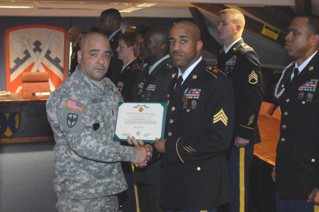 Command Sgt. Maj. Ismael Rodriguez, the command sergeant major of the 16th Sustainment Brigade, awards the Army Achievement Medal to Sgt. Corey Thompson, a motor transport operator with 1st Inland Cargo Transfer Company, 18th Combat Sustainment Support Battalion, 16th Sust. Bde., for winning Warrior Leader of the Quarter.