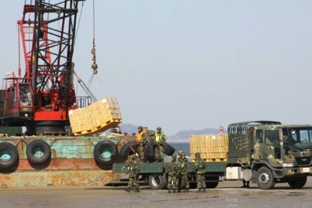 Republic of Korea soldiers and sailors work together to unload pallets of equipment from a barge during the Combined Joint Logistics Over-the-Shore training exercise at Anmyeon Beach, March 23.