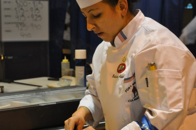 Pfc. Deborah Adams, junior chef competitor for the Fort Bragg Culinary Arts Team, slices her chicken sausage during the junior chef portion of the 36th Annual Armed Forces Culinary Arts Competition at Fort Lee, Va., March 7. Adams had only one hour to create all the different elements of her stuffed chicken meal for two. The meal earned her a gold medal in the competition. Fort Bragg won 2nd place in the competition.