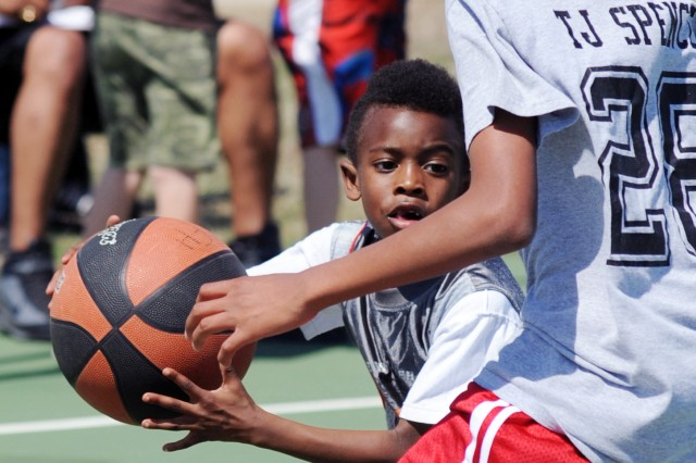 Justice Henderson, 7, looks for an opening against a taller player March 18, during 3-on-3 games held as part of the Kouma Classic basketball tournament at Fort Hood, Texas.