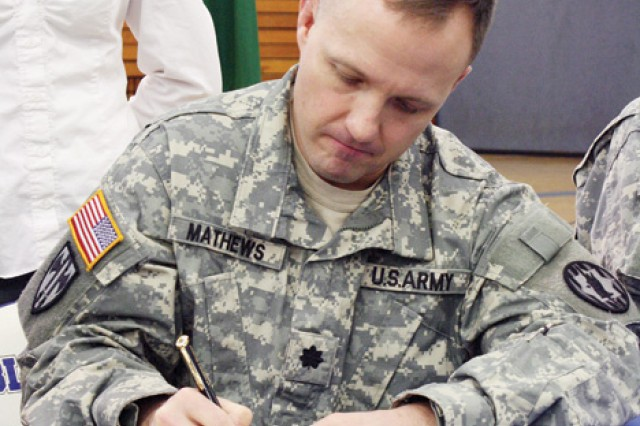 Lt. Col. Michael Mathews, commander, 97th MP Bn., signs the partnership charter between the military police battalion and JCHS March 18 during a signing ceremony at the school.