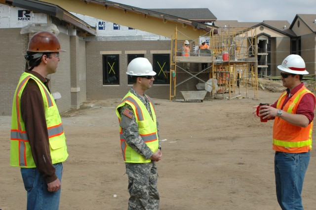 FORT BRAGG, N.C. (MARCH 27, 2011) - George V. Blackard of the U.S. Army Corps of Engineer's Fort Bragg Area Office (right) reports to The Army Ground Forces Band's commander, Maj. Treg Ancelet, on how work is progressing on the band's new training facility here as Stephen Nunn, project manager for the building's prime contract design-builder, Lifecycle Construction Services, listens. The state-of-the-art structure is right on schedule for turnover in late June.