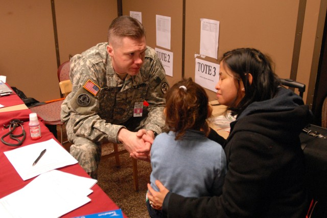 A medic meets with family members as they process through the Joint Reception Coordination Center inside the Seattle-Tacoma International Airport, Wash., March 22, as part of a Voluntary Authorized Departure from Japan. U.S. Army North is heading up operations to welcome home the family members as the supporting command for U.S. Northern Command at three Joint Reception Coordination Centers in the continental United States. The other two sites are Travis Air Force Base in Fairfield, Calif., and Denver International Airport.