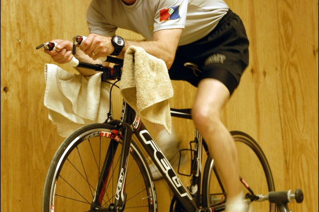 Capt. Douglas 'Doc' Powell, brigade surgeon assigned to Headquarters and Headquarters Detachment, 1st Brigade Combat Team, 4th Infantry Division, conducts physical fitness March 23, within the confines of his small office at Camp Nathan Smith. Powell met his wife, world-class triathlete Heidi Grimm, during a 100-mile bike ride in Colorado Springs, Colo. Powell is an avid outdoorsman, having competed on the U.S. Army's winter biathlon team in Vermont, as well as the Army 10-miler team at Joint Base Lewis-McChord, Wash. Powell left his job as a business executive for Burton Snowboards at the age of 40 to attend medical school and become a doctor for the U.S. Army.  He is currently serving at Camp Nathan Smith in order to oversee operations at the Troop Medical Clinic there.