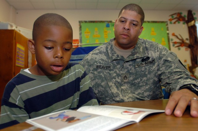 "FORT HOOD, Texas, March 25, 20111-Warrior Transition Brigade (WTB) cadre, Staff Sgt. Marcel Weaver, reads to his 7-year-old son, Marco, during the brigade's Adopt A-School recent reading night at Fort Hood Clark Elementary School. Weaver was one of several WTB Soldiers participating in the reading event in honor of National Reading Month, held annually in March to honor the birth of Theodor Geisel, otherwise known as Dr. Seuss. An avid reader, Weaver and his wife promote reading at home with 7 p.m. mandatory reading hour for all family members. At that time, Weaver and his family turn off the cell phones, televisions and computers to devote an hour to reading. Although he and his wife always have been avid readers, the couple made it a mandatory family event after reading research papers written by high-school honor-roll students and discovering many of them couldn't write a complete sentence, in addition to demonstrating inadequate grammar skills.  Weaver is from Washington, D.C. and enjoys reading because ""brings life to words"" and allows him to experience something new every time he turns the page. (WTB photo by Gloria Montgomery)"