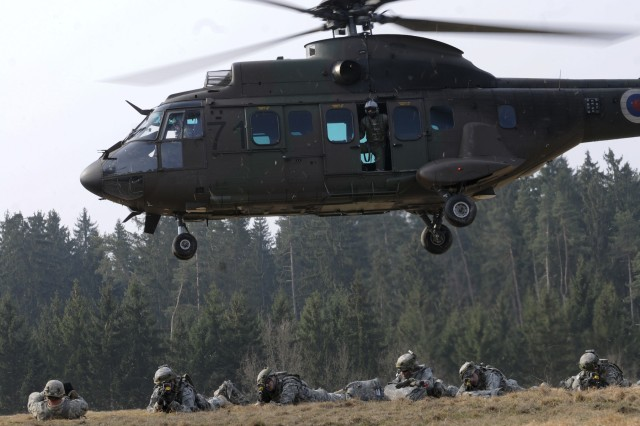 HOHENFELS, Germany - Soldiers with U.S. Army Europe's 1st Battalion, 2nd Infantry, 172nd Infantry Brigade, establish security at their landing zone after being dropped off by a Slovenian Cougar helicopter during an air assault operation at Grafenwoehr Training Area, Germany, March 27. The Soldiers of the 172nd are participating in a Mission Rehearsal Exercise at the Joint Multinational Readiness Center here through April 8. For more photos of the exercise, and other USAREUR images, visit the USAREUR Flickr gallery at www.flickr.com/photos/usareur_images