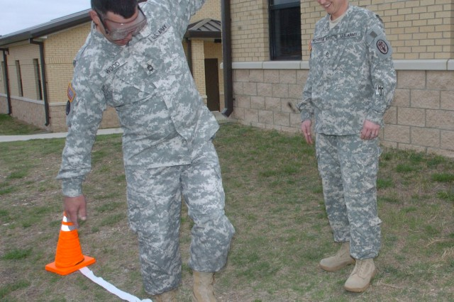FORT HOOD, March 25--Trying to walk a straight line wearing visual impairment goggles is Sgt. 1st Class Greg Wood, who is assigned to the Warrior Transition Brigade. Looking on is Staff Sgt. Machin McHargue,  a squad leader for C Co., 1st Bn., WTB, who helped organize the company's Safety Stand Down Day training, which was observed brigade-wide March 25.  The goggles simulate the effects of alcohol impairment equal to nearly double the legal limit. Soldiers also received awareness training in motorcycle, boating and automobile safety. Safety stand down days are held Army wide several times a year and promote recreational and workplace safety. (Photo by Gloria Montgomery, WTB PAO)