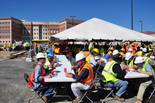 An estimated 300 craft workers enjoy a celebratory lunch, March 24, near the staff entrance to the FORSCOM/USARC Combined Headquarters Construction Project, at Fort Bragg, N.C.  They had gathered to recognize the many safety, quality and timeline successes of the project, during a barbecue lunch for an estimated 300 craft workers at the site. Work on the project is nearing completion and on schedule for a June 21 turnover to the U.S. Army.
