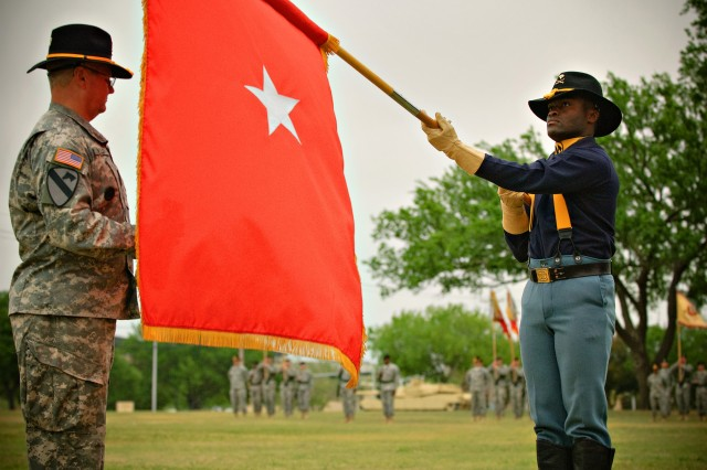 """FORT HOOD, Texas-Spc. Bayee Besong (right), of Denver, Colo., an administrative assistant to the 1st Cavalry Division's command group, presents the one star flag to the Command Sgt. Maj. Rory Malloy for """"uncasing."""" The uncasing of the one-star flag signifies that the division has a deputy commander sitting in the rank of brigadier general."""