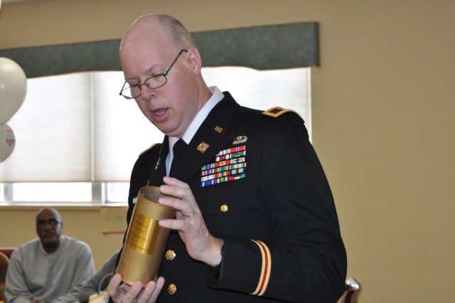 Col. Arnold P. Montgomey, chief of staff, Joint Munitions Command, recalls the significance of the 75 mm artillery shell he presents to Mr. Shelby Harris. The 75 mm artillery shell was commonly used during World War II.  During the war effort, the shell was produced by Kingsbury Ordnance Plant in LaPorte, Ind., some five and a half hours north of Harris' hometown of Ayrshire, Ind.