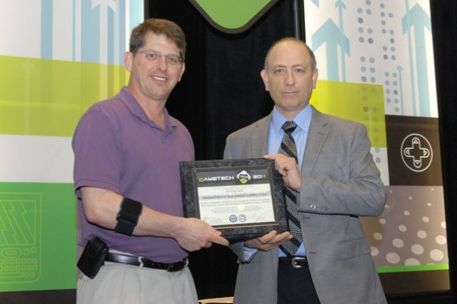 "Frank DiGiovanni (right), the director of training, readiness and strategy, Office of the Deputy Assistant Secretary of Defense (Readiness) presents the 2011 Department of Defense award ""Innovations in Department of Defense Gaming"" to Mark Covey, Systems Integration, Modeling and Simulations Director for the U.S. Army Training and Doctrine Command's JTCOIC, at the GameTech 2011 conference in Orlando, Fla. last week."