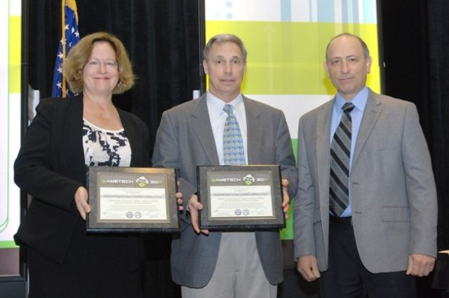 "Frank DiGiovanni (right), the director of training, readiness and strategy, Office of the Deputy Assistant Secretary of Defense (Readiness) presents the 2011 Department of Defense award ""Innovations in Department of Defense Gaming"" to Dr. Marjorie Zielke (left), assistant professor of Arts and Technology (ATEC) at the University of Texas, Dallas, and Ben Jordan, director of Modeling and Simulation for the U.S. Army Training and Doctrine Command's Intelligence Support Activity (TRISA), at the GameTech 2011 conference in Orlando, Fla. last week."