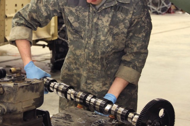 JOINT BASE ELMENDORF-RICHARDSON -- Spc. Adam R. Powell inspects a crank shaft from an M1083 engine for deficiencies March 17 at the 6th Engineer Battalion Motor Pool.