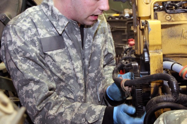 JOINT BASE ELMENDORF- RICHARDSON -- Spc. James D. Johnson, a wheeled vehicle repairer with Forward Support Company, 6th Engineer Battalion, pulls a crank shaft from an M1083 engine March 17 at the 6th Engineer Battalion Motor Pool here.