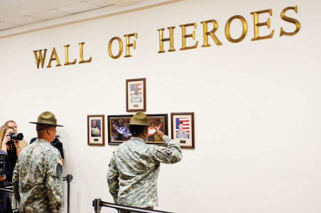 Members of the 198th Infantry Brigade Honor Guard stand at attention March 22 in front of the Wall of Heroes during the dedication to fallen Soldiers at the Survivor Outreach Services center.