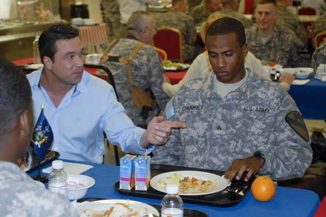 CONTINGENCY OPERATING BASE BASRAH, Iraq - Sgt Charlito Chumney (right), a combat engineer in Headquarters and Headquarters Company, 1st Battalion, 12th Cavalry Regiment,  3rd Advise and Assist Brigade, 1st Cavalry Division, of Harlem, N.Y., converses with Rep. Michael Grimm, R-N.Y., during a congressional delegation luncheon in Basrah, Iraq.