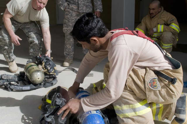 With the help of an interpreter, Air Force Master Sgt. Jason Berry, 738th Air Expeditionary Advisory Group fire protection adviser, inspects fire safety equipment with Afghan Kandahar Air Wing firefighters before conducting their first live-burn training exercise at Kandahar Airfield, Afghanistan, March 28, 2011. Sergeant Berry deployed from the 48th Fighter Wing, Royal Air Force Lakenheath, England