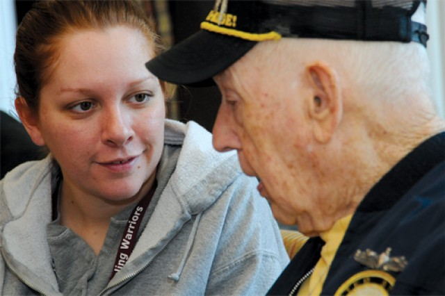 Sgt. Tessa Wilburn of MEDDAC listens to World War II veteran James Fugett. Wilburn and other BOSS participants visited the Sitter and Barfoot Veterans Care Center in Richmond March 29 as a part of its community outreach program.