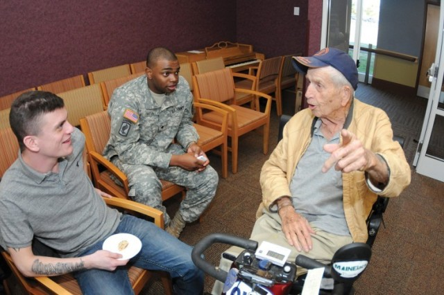 """Boss participants Spc. Michael Nelson and Spc. Dwight Smith listen to self-described """"comedian"""" Gordon McCandless at the Sitter and Barfoot Veterans Care Center March 29. They visited the Richmond facility as part of their community outreach"""