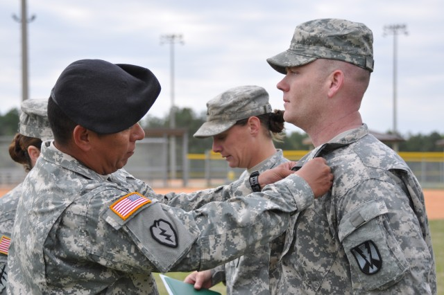 "Sgt. 1st Class Scott Wilkie, Company E, 3rd Battalion, 34th Infantry Regiment, right, receives his Expert Infantryman Badge in a ceremony Friday, at Hilton Field Softball Complex. Wilkie was the only candidate designated ""true blue,"" meaning he made no mistakes during the testing."