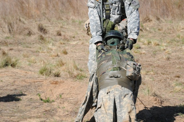 "Staff Sgt. Daniel Lazinek, 4-10th, evacuates a ""casualty,"" which is one of the 10 tasks Expert Infantryman Badge candidates had to perform within 20 minutes during the patrol lane portion of the testing."