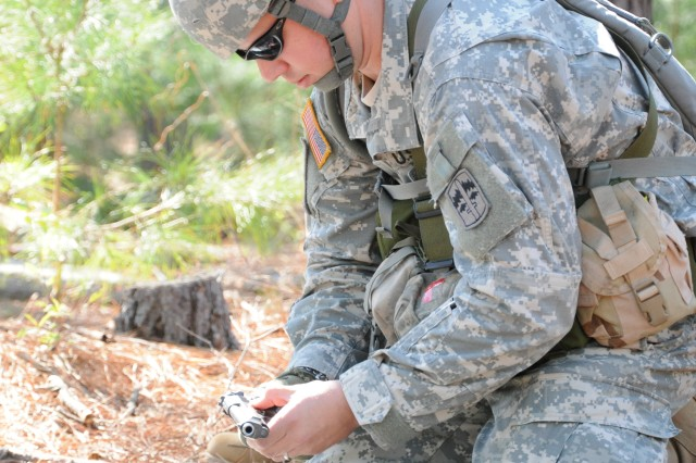 Staff Sgt. Daniel Lazinek, Company B, 4th Battalion, 10th Infantry Regiment, performs a functions check on an M9 pistol during Expert Infantryman Badge testing, March 24.