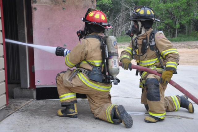A pair of firefighters work on putting out the burn room blaze during a live fire demonstration March 29 at their new training facility on Fort Sam Houston.