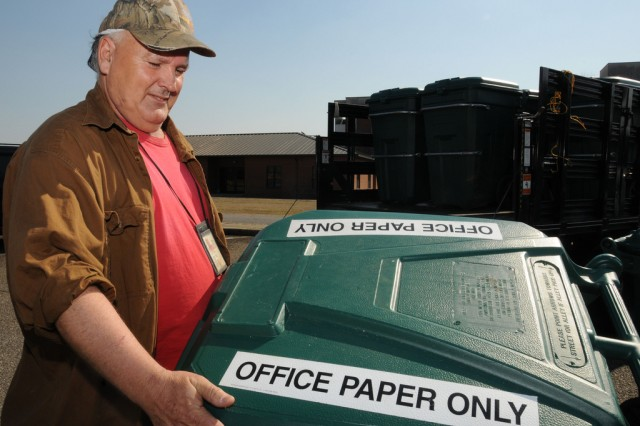 Earl Rogers loads a container of recyclable office paper into the back of his truck during his weekly rounds for the post's Qualified Recycling Program.