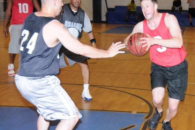Jay Irwin, Showstoppers player, charges through Mike Kelly, USAAMC player, and goes in for the score during an intramural basketball game at Fortenberry-Colton Physical Fitness Facility March 28. The Showstoppers won, 60-48.