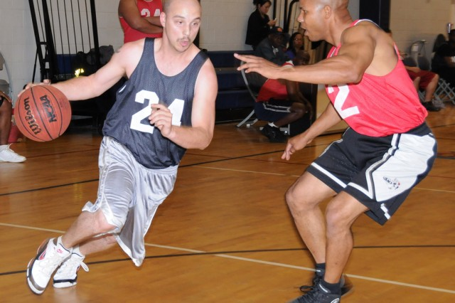 Mike Kelly, USAAMC player, tries to run by Hubert Agard, Showstoppers player, during an intramural basketball game March 28 at Fortenberry-Colton Physical Fitness Facility. The Showstoppers won, 60-48.