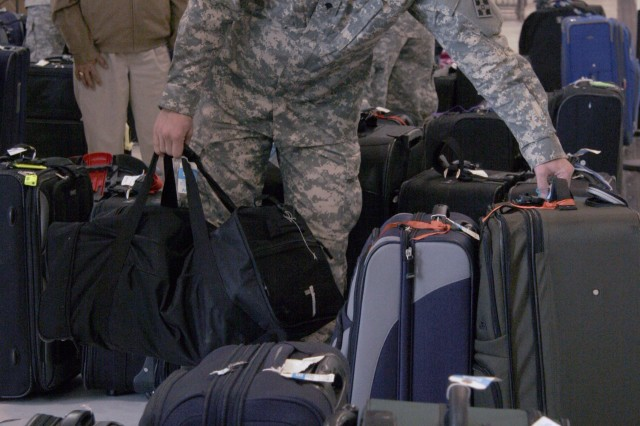 Spc. Matthew Davis, 3rd Squadron, 61st Cavalry Regiment, 4th Brigade Combat Team, 4th Infantry Division, helps American military families stationed in Japan find their luggage at the Denver International Airport during the families' evacuation March