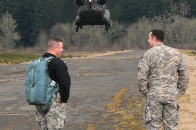 Master Sgt. Mark Dasch, left, watches a CH-47 Chinook helicopter land March 18, near Rogers Drop Zone, Joint Base Lewis-McChord, Wash.