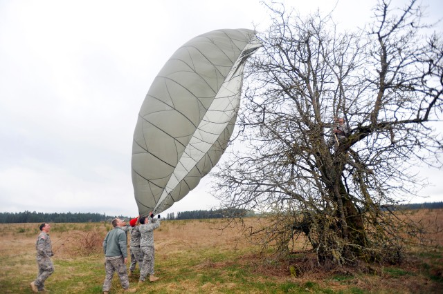 Soldiers attempt to free a parachute from a tree March 18, near Rogers Drop Zone, Joint Base Lewis-McChord, Wash. During the jump for the Verbally Initiated Release System exercise, parachutist 1st Lt. John Gomen, C Co., 38th Long Range Surveillance, landed, but didn't quite reach the ground. He ended up coming in backwards, and didn't know he was about to hit a tree until he was in it.