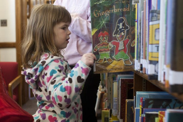 Four-year-old Langley Amiss checks out a shelf of children's books at the Medal of Honor Memorial Library's grand reopening March 25. The library staff formally welcomed the Fort Meade community back to the facility after new carpeting was installed and 12 bookshelves were reconfigured.