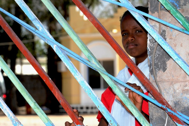 A young girl watches from the Dikhil Hospital entrance gate as seven cisterns are delivered to the hospital on March 22. The seven cisterns, purchased by the 402nd Civil Affairs Battalion, will benefit roughly 88,000 people in the region who use the Dikhil Hospital and its outlying village clinics. The increased water storage capacity will help medical staff improve hygiene and reduce infections and maternal death rates.