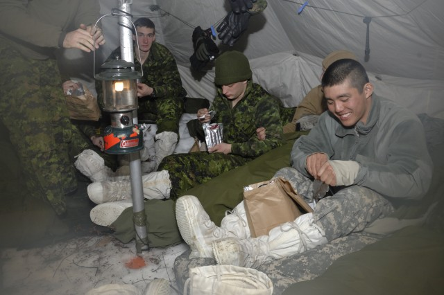 GOGAMA, Ontario-- New York Army National Guard Spc. Masami Yamakado, New York City resident and member of the 1st Battalion 69th Infantry headquarters sniper team, chows down on Canadian rations with members of the Cameron Highlanders of Ottawa, a Canadian Army Reserve unit, during winter survival training here on MArch 15. Yamakado and eight other members of the 69th Infantry, almost all of them from New York City, participated in Exercise Wolfpack Endeavour 2011 from March 7-21 in which they learned winter survival and combat skills with their Canadian counterparts.