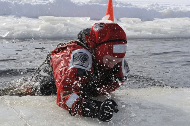 GOGAMA, Ontario--A Soldier dressed in a rescue suit pulls himself out of icy water during winter survival training conducted by the Canadian Army Reserve's 33rd Canadian Brigade Group here, March 7-21. Nine members of the New York Army National Guard's 1st Battalion 69th Infantry participated in the training exercise.