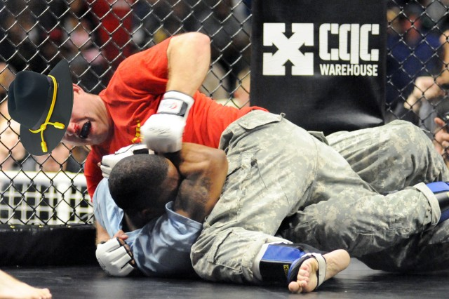 The Army Combat Stetson, depicted here atop a Soldier competing in an Army combatives tournament, is expected to invoke fear in America's enemies.  Note, it will be worn without any pin-on rank or regalia to avoid causing cruel or unusual wounds on enemy forces who are unfortunate enough to find themselves in hand-to-hand combat with a Soldier.  Pounding armed enemy forces senseless while staying and looking cool will still be allowed.