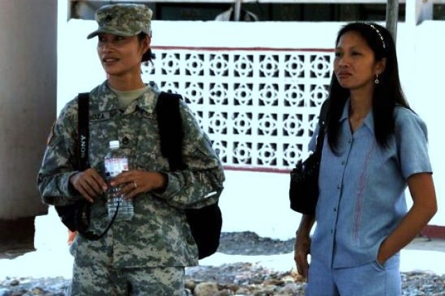 ChaplainAca,!a,,cs assistant U.S. Army Staff Sergeant Marie Lanoza observes the official groundbreaking ceremony for the construction of two new classrooms with one of the teachers at Taposo Elementary School in Zambales province during  Balikatan 2011.