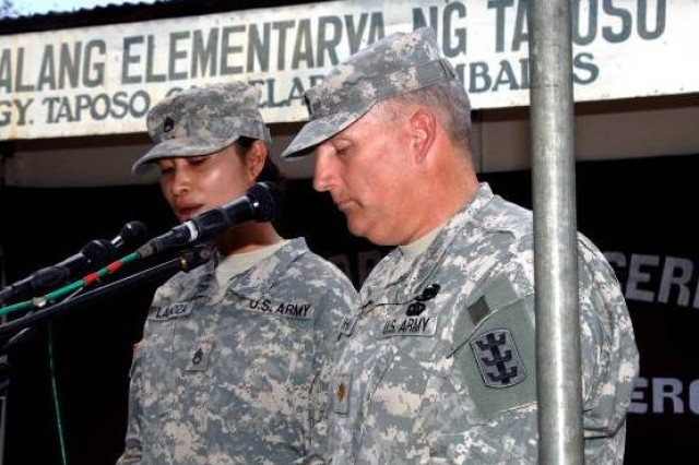 Chaplain assistant U.S. Army Staff Sergeant Marie Lanoza, translates U.S. Army Chaplain (Maj.) David Shoffner's benediction into Tagalong for the community at the official groundbreaking ceremony for construction of two new classrooms at the Taposo Elementary School in Zambales province during Balikatan 2011. Balikatan is a bilateral annual military exercise between the Republic of the Philippines and the United States. Humanitarian assistance and training activities enable service members of both countries to train together, improve military readiness, and provide assistance in local communities.
