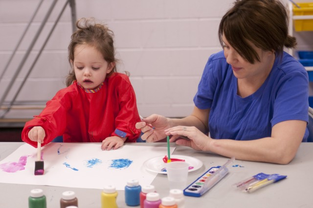Isabella Young, 2, paints a picture while her mom, Krystyna, helps during a mommy and me, Mini Monet class, March 22.