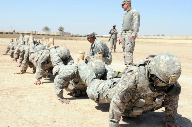 """BABIL, Iraq - Soldiers of Regimental Support Squadron, 3rd Armored Cavalry Regiment, wearing their full combat uniform and chemical mask, attempt a team push-up during a """"Spur Ride"""" on Contingency Operating Site Kalsu March 18, 2011. The Soldiers completed an all day event that tested their mental and physical limits for a place amongst the ranks of the """"Order of the Spur"""", a cavalry tradition that dates back to its origin. US Army photo by Staff Sgt. Garrett Ralston (110318-A-8856R-179)"""