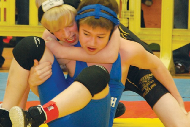 Stuttgart's C.J. Berg (left), 11, puts Ansbach's Chase O'Gorman, 11, in a headlock at the Child, Youth and School Services regional wrestling tournament, held March 26 at the Patch High School gym.