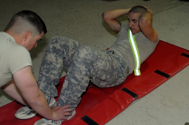 CONTINGENCY OPERATING BASE ADDER, Iraq - Spc. Julian McKinnon, with Headquarters and Headquarters Battery, 2nd Battalion, 82nd Field Artillery Regiment, 3rd Advise and Assist Brigade, conducts the sit-ups portion of an Army physical fitness test during a Soldier/Non-Commissioned Officer of the Quarter competition March 31 on Contingency Operating Base Adder. McKinnon went on to win the Soldier of the Quarter Award.