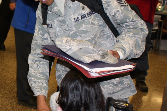 Minutes after their arrival at Seattle-Tacoma International Airport, Air Force Staff Sgt. Nicole Powell and her two-year-old daughter are greeted by USO volunteers.