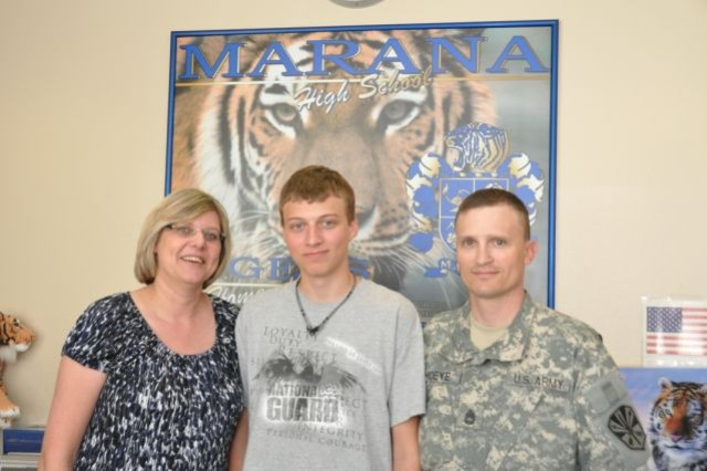 """The Hoeyes, from left, mom Michaelena, Army Child of the Year Kyle, and dad Sgt. 1st Class James showing their """"Tiger Pride"""" at Marana (Ariz.) High School. The school administration and staff is very supportive of Kyle's efforts to help dependent military children, and said they are very proud of Kyle's selection as Army Child of the Year."""