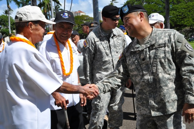 Lt. Col. Kimo Dunn, commander of the 100th Battalion, 442nd Infantry Regiment, greets World War II veterans March 28, at Iolani Palace in Honolulu.